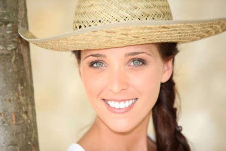Vrouw in strooien hoed stellen door boom Stockfoto