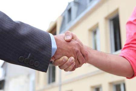 real estate sold: Pareja d�ndose la mano fuera de una casa Foto de archivo