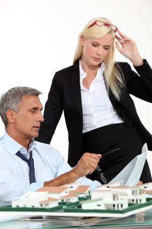 a boss and his female assistant thinking behind a subdivision model photo