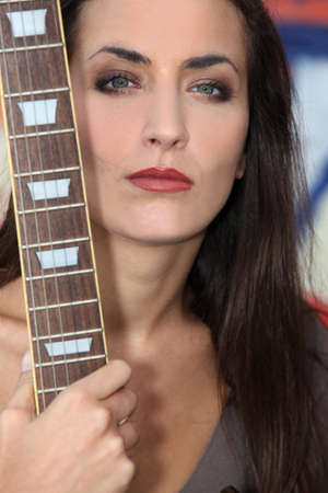 withdrawn: Unfriendly woman posing with her guitar Stock Photo