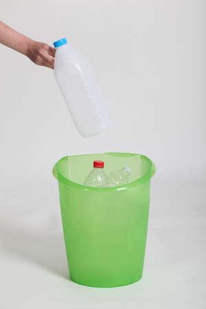 Woman placing plastic bottle into green bin photo