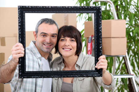 unpacked: a couple is holding and posing behind a painting frame inside an apartment full of unpacked packages