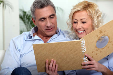 Smiling man and woman watching a photo album Stock Photo - 13560301