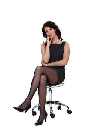piernas con tacones: Mujer sentada en la silla Foto de archivo