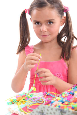 Little girl making necklace photo