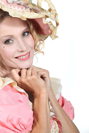 bonnet up: Woman in a theatrical pink and cream dress and bonnet