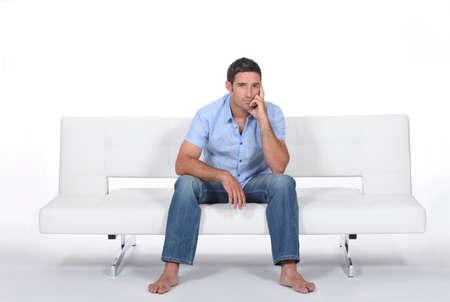 bloke: handsome bloke sitting on sofa Stock Photo