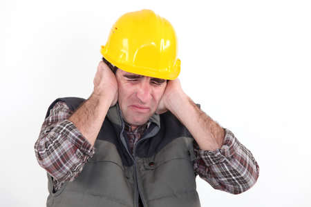 deafening: Construction worker holding his hands over his ears