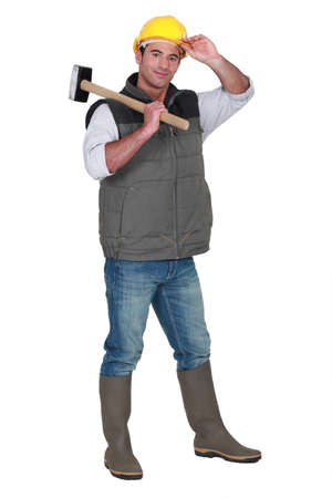 non verbal communication: Tradesman carrying a mallet and wearing a hard hat and rubber boots