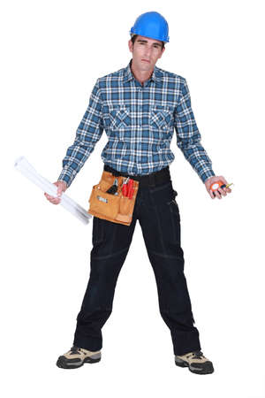 Unhappy tradesman holding his tools and rolled-up drawings photo