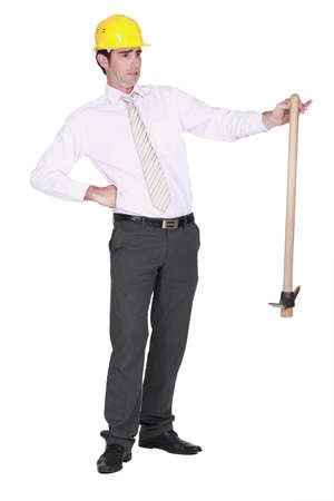 Architect sheepishly holding pick-axe Stock Photo - 13561318