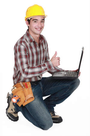 qualified worker: Happy builder with laptop giving the thumbs-up Stock Photo
