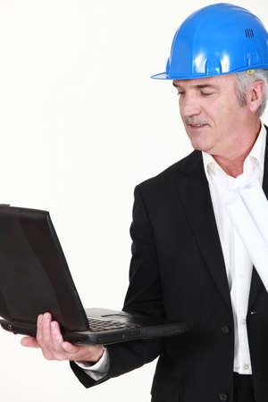 Engineer holding his laptop and rolled-up drawings Stock Photo - 13560930