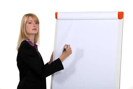 Blond businesswoman à écrire sur tableau blanc