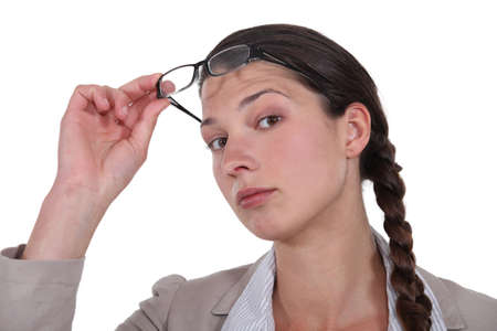 verifying: Curious brunette lifting her eyeglasses Stock Photo