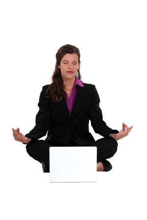 Businesswoman meditating in  front of laptop photo
