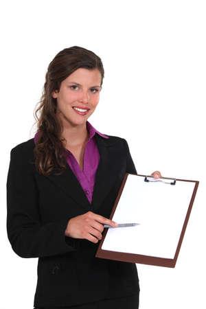 A businesswoman presenting a clipboard  photo