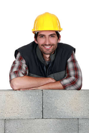 Smiling tradesman leaning on a stone wall photo