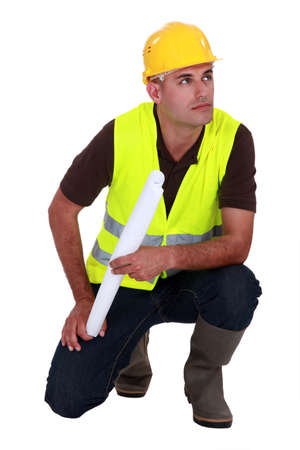 Engineer in a reflective vest with plans photo