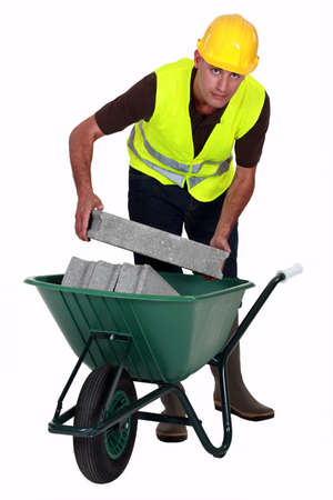 barrow: Mason carrying bricks in wheel barrow