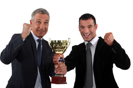 gratified: businessmen holding a golden cup Stock Photo