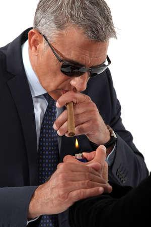 businessman wearing sunglasses and smoking a cigar photo