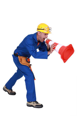 Construction worker shouting into a traffic cone photo