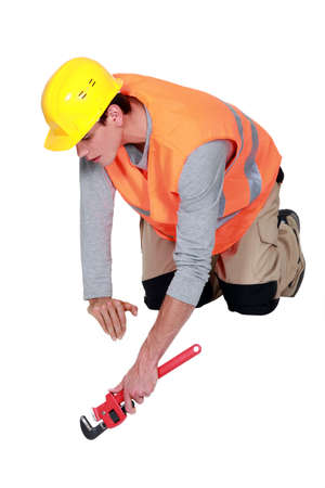 knees bent: Tradesman using a pipe wrench