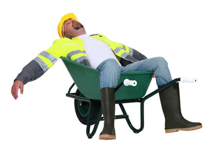 Tradesman asleep in a wheelbarrow Stock Photo