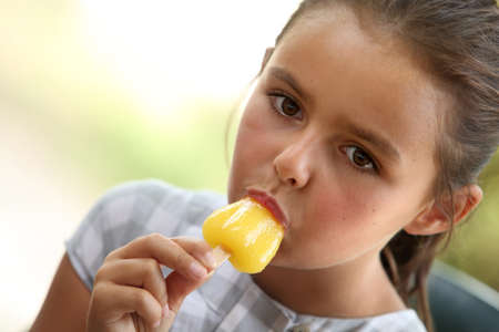 indulging: Little girl with ice lolly Stock Photo