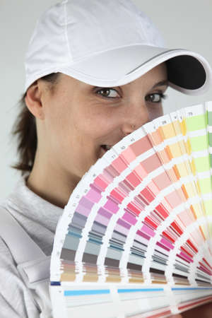 Female decorator choosing color from swatch photo