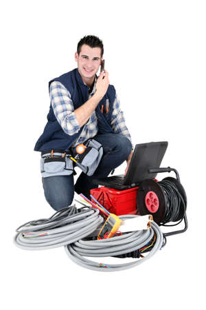 journeyman: Electrician making a call whilst kneeling by his equipment Stock Photo