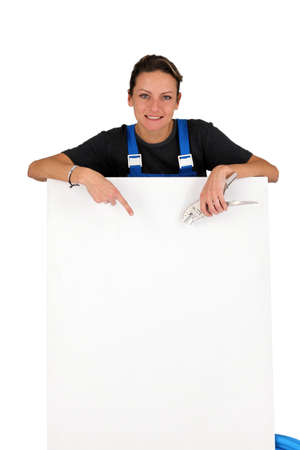 Female electrician pointing at blank board Stock Photo - 13583273