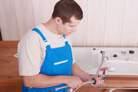 Plumber fitting a tap on a kitchen sink