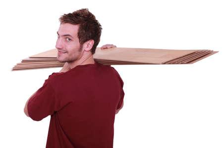 self dependent: Man carrying parquet slats