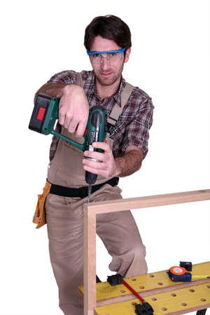 screwing: Carpenter screwing a frame together