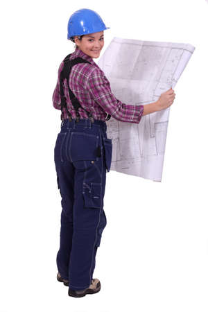female construction worker watching a blueprint Stock Photo - 13583798