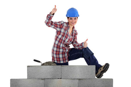 female mason sitting on a wall making thumbs up sign photo