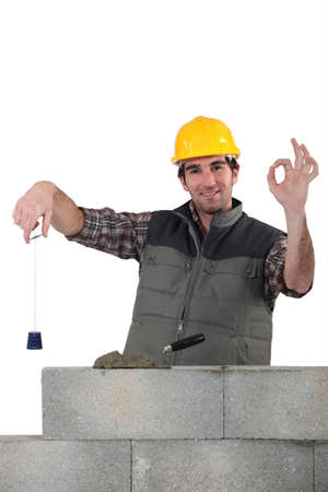 Bricklayer with a plumb line photo