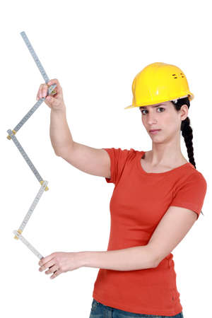 poker faced: Construction worker holding a ruler Stock Photo