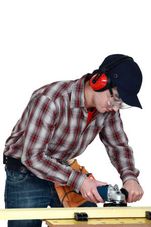 woodworker: Man using router on plank of wood