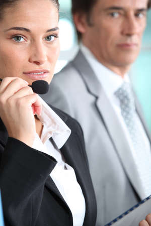 Woman with a headset being watched by her boss photo