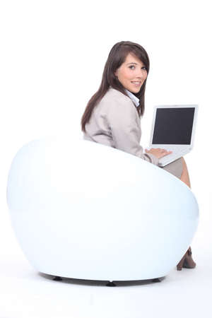 Young woman in  a funky white chair, using a laptop computer Stock Photo - 13584034