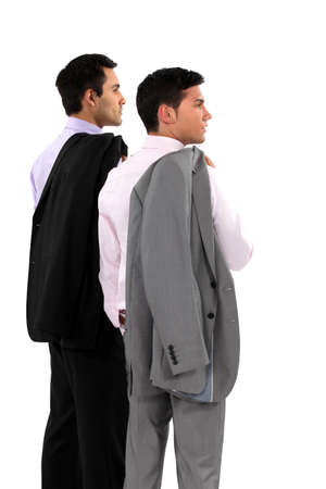 looking over shoulder: Two businessmen with their jackets over their shoulders