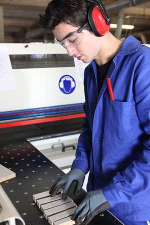 Young factory worker preparing machine photo