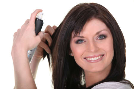 brown hair blue eyes: Woman applying hairspray