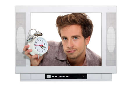 Man holding alarm clock trapped in the television Stock Photo - 13582279