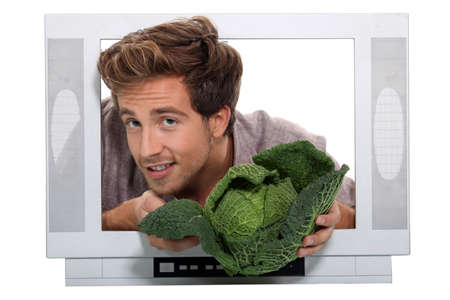 angry vegetable: Man holding cabbage escaping from television
