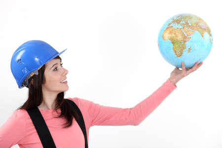 Tradeswoman holding up a globe photo