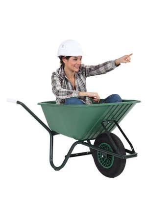 tradesperson: Female tradesperson sitting in a wheelbarrow